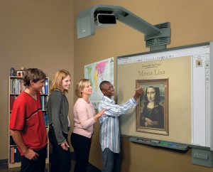A group of students lined up and far too happy to be using a smartboard